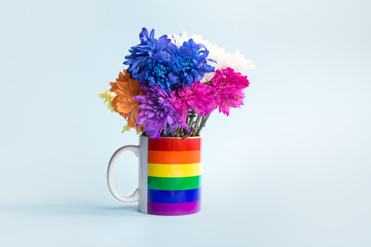 A mug painted in LGBT rainbow on a blue background as a vase, withered wilted flowers of different colors.