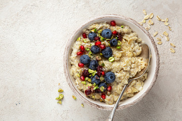 Oatmeal porridge with fresh berry, nuts and honey in bowl