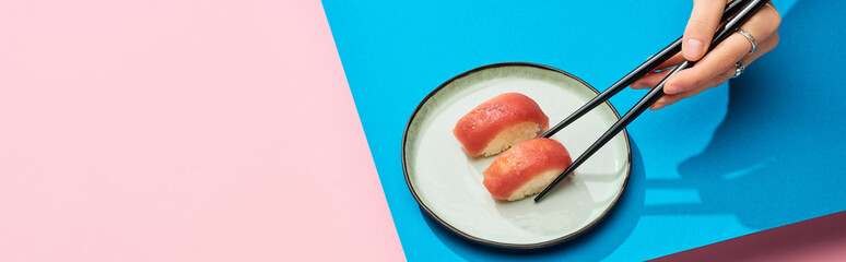 Foto op Plexiglas Sushi bar partial view of woman eating fresh nigiri with tuna with chopsticks on blue, pink background, panoramic shot