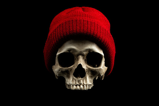 Human skull wearing red winter hat isolated on black background. Cold weather concept.