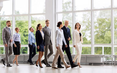 people, work and corporate concept - happy business team walking along office building and talking Fotomurales