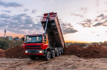A dump truck is dumping gravel on an excavation site