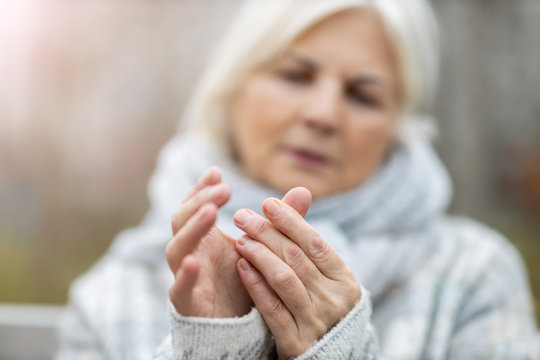 Senior woman with arthritis rubbing hands
