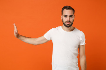 Young man in casual white t-shirt posing isolated on bright orange wall background studio portrait. People sincere emotions lifestyle concept. Mock up copy space. Showing stop gesture aside with palm. Wall mural