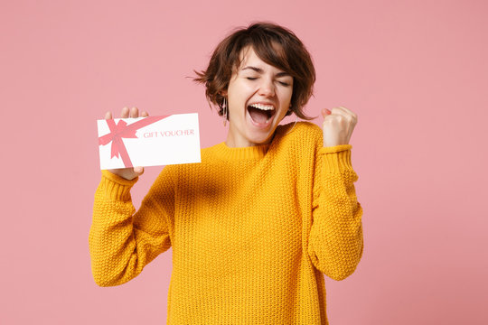 Joyful young brunette woman girl in yellow sweater posing isolated on pastel pink background studio portrait. People lifestyle concept. Mock up copy space. Hold gift certificate, doing winner gesture.