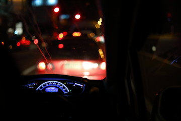 Fotomurales - people driving car on night road, traffic jam in the city