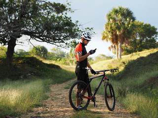 Sports, active lifestyle and modern technology. Outdoor picture of cyclist on mountain bike using navigator on smart phone, exploring map and searching GPS coordinates while biking in countryside.