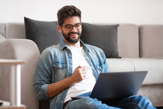 Smiling caucasian hipster sitting on floor in living room, holding laptop in lap and using credit card for online shopping or paying bills.