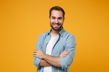 Smiling young bearded man in casual blue shirt posing isolated on yellow orange wall background, studio portrait. People sincere emotions lifestyle concept. Mock up copy space. Holding hands crossed. Papier Peint