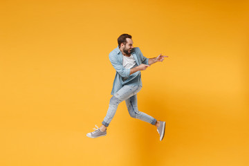 Funny young bearded man in casual blue shirt posing isolated on yellow orange background, studio portrait. People emotions lifestyle concept. Mock up copy space. Jumping pointing index fingers aside.