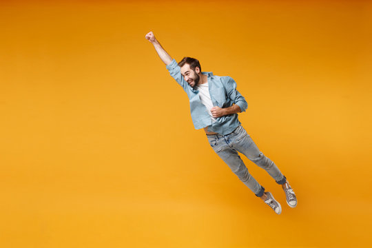 Funny young bearded man in casual blue shirt posing isolated on yellow orange background, studio portrait. People lifestyle concept. Mock up copy space. Jumping with outstretched hand like Superman.