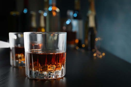 Glasses of whiskey on bar counter, close up and space for text