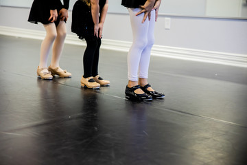 young girls with tap shoes on dance class floor