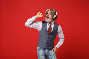 Cheerful elderly gray-haired mustache bearded man in classic shirt vest and tie posing isolated on red background. People lifestyle concept. Mock up copy space. Listen music with headphones, singing.