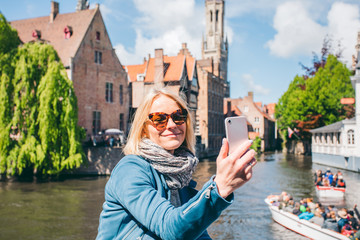 Door stickers Bridges Beautiful young girl takes selfie photo on the background of the famous tourist destination with a canal in Bruges, Belgium