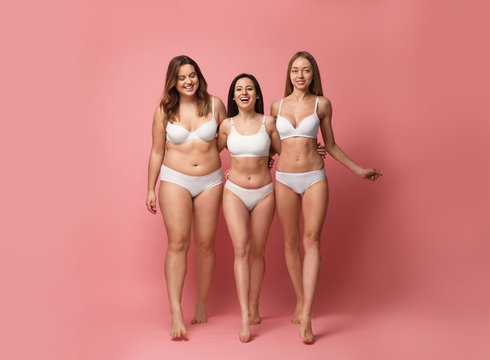 Group of women with different body types in underwear on pink background