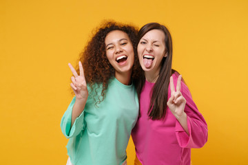 Two cheerful women friends european and african american girls in pink green clothes posing isolated on yellow orange background. People lifestyle concept. Mock up copy space. Showing victory sign.