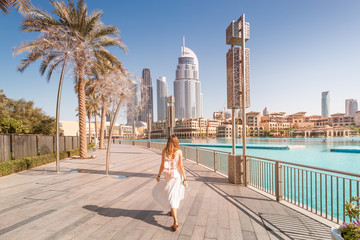 Spoed Fotobehang Dubai Happy tourist girl walking near fountains in Dubai city. Vacation and sightseeing concept