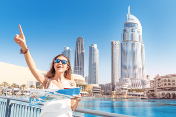 Happy tourist girl with map travels in Dubai city, United Arab Emirates. Vacation and sightseeing concept Wall mural