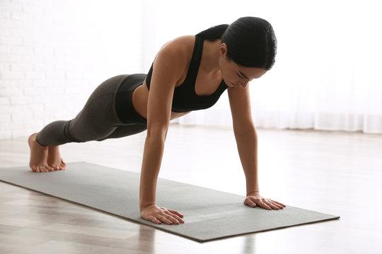 Young woman practicing plank asana in yoga studio. Phalankasana pose