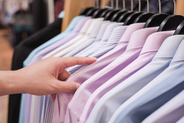 Cropped Hand Of Man choosing Men's shirts in clothing store