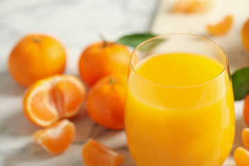 Glass of fresh tangerine juice and fruits on marble table, closeup