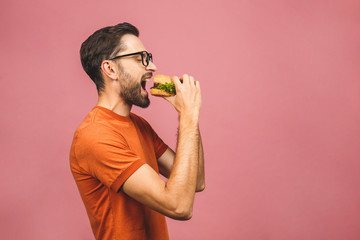 Young man holding a piece of hamburger. Student eats fast food. Burger is not helpful food. Very hungry guy. Diet concept. Isolated over pink background. Papier Peint