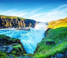 Foto auf Leinwand Blau Magical charming bright colorful landscape with a famous Gullfoss waterfall and meadow with flowersin Iceland. Exotic countries. Amazing places. Popular tourist atraction.