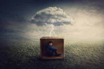 Surreal concept with a scared guy shelters inside a cardboard box. Introvert man caged by own fears as a thunderstorm cloud trapped him under the rain. Mysterious storm as emotional crisis symbol.