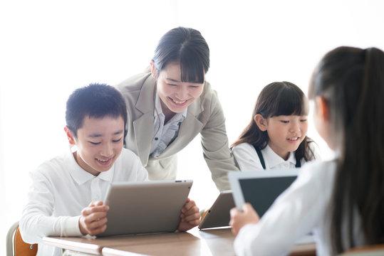 先生にプログラミングの勉強を教わる小学生  AR