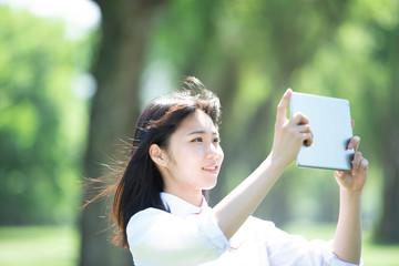ポプラ並木でタブレットPCを持つ女子学生
