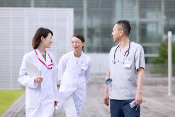 歩きながら会話をする医師たち