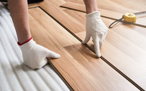 Installing laminated floor, detail on man hands in gloves fitting wooden tile, over white foam base layer, tape measure in background