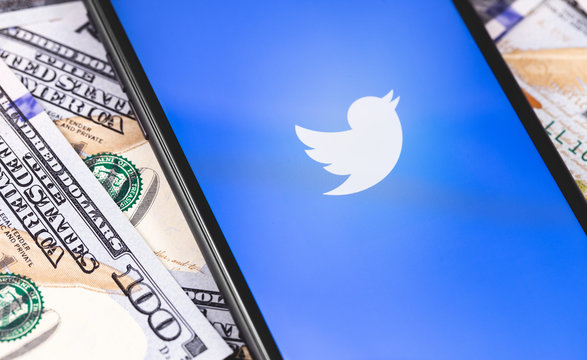 Twitter logo on the screen smartphone and money, dollars. Twitter is a social media online service for microblogging and networking communication. Moscow, Russia - March 1, 2019