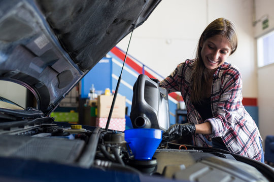 Smiling casual woman in gloves holding can of engine oil and pouring it through funnel into car working in service