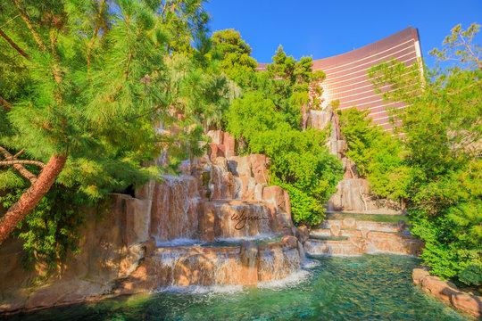 Las Vegas, Nevada, United States - August 18, 2018: Wynn Las Vegas Waterfall Fountain. The Wynn is Resort Hotel 5-star casino, Las Vegas Strip. Beautiful falls in the garden outdoors in blue sky day.