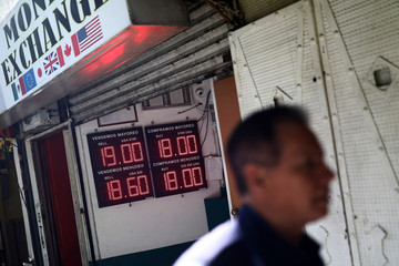 A man walks past a board displaying the exchange rate for Mexican Peso and U.S. Dollar at a currency exchange shop in Mexico City
