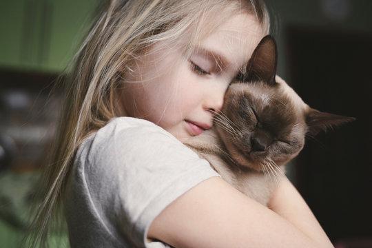 Little girl cuddling with her Burma cat