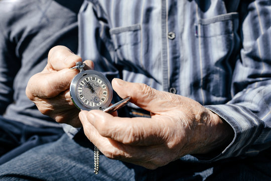Old man's hands holding silver pocket clock, close-up