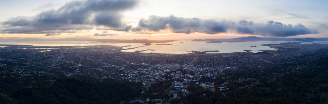 A serene sunset illuminates the densely populated San Francisco Bay area including Oakland, Berkeley, Emeryville, El Cerrito, and San Francisco in the distance.