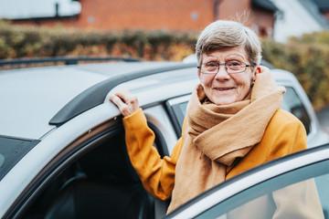 Senior woman near car