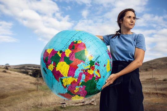 Mature woman holding inflatable globe, looking confident
