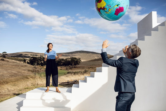 Businessman and woman playing with inflatable globe