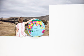 Little girl sitting on wall, with arm aroung inflatable globe, rear view