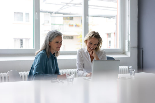Two businesswomen using laptop at desk in office together