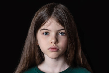 Closeup portrait of serious, sad little girl isolated on black background