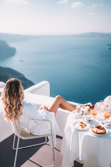 Aluminium Prints Santorini Young woman with blonde hair having breakfast in santorini greece