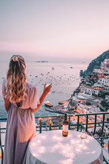 Young woman with blonde hair on balcony in Positano italy