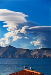 Croatia, Kvarner Gulf, Baska, Clouds and coast, doves on roof
