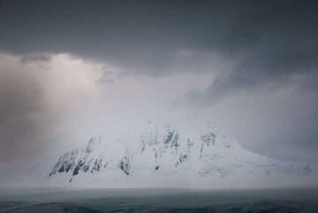 Keuken foto achterwand Antarctica Antarctica covered in the snow surrounded by water under a cloudy sky
